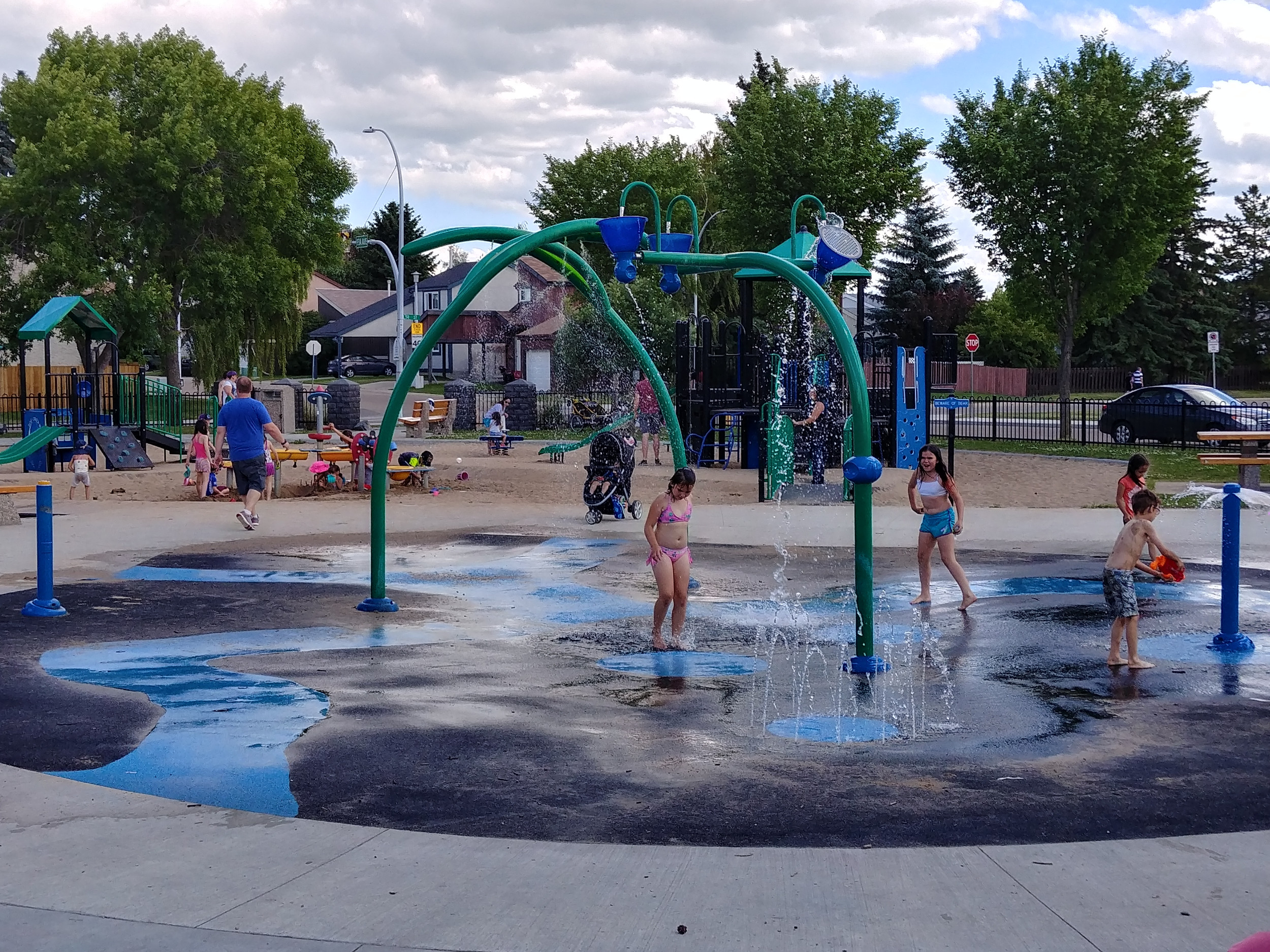 children playing in a spray park beside the community league