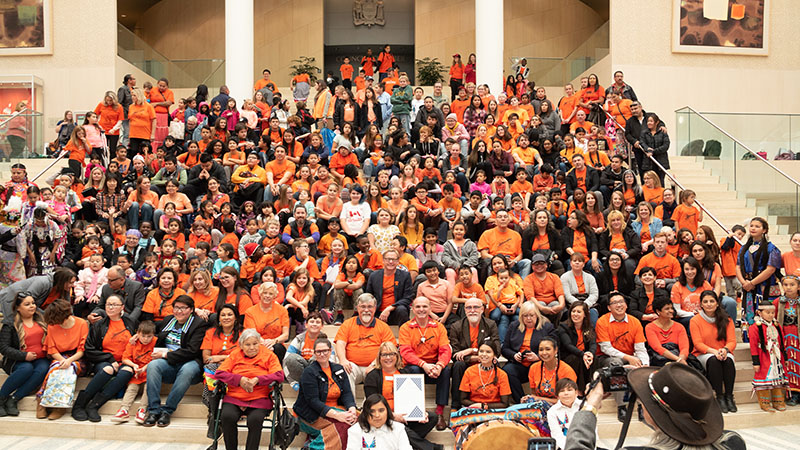 A photo of people gathered on the city steps wearing orange shirts
